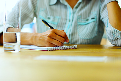 Closeup portrait of a female hand writing on a paper
